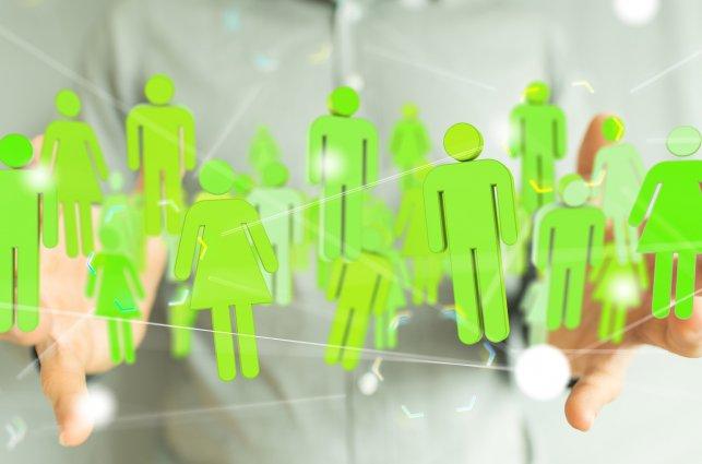 Na zdjęciu dłonie i wiele zielonych ludzików jakby wycietych z papieru