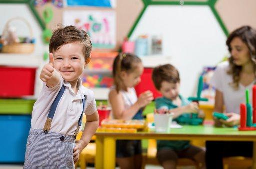 zdjęcie przedstawia chłopca z wystawionym w górę kciukiem