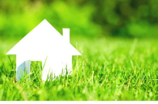 biały domek na zielonej trawie