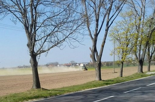 Po wysuszonym polu jedzie traktor, strasznie kurzy