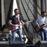 zdjęcie przedstawia gitarzystów na scenie