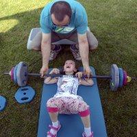 zdjęcie przedstawia dziewczynkę, która przy pomocy taty podnosi cieżar