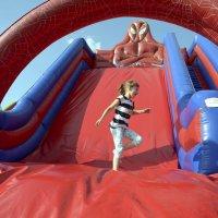 zdjęcie przedstawia dziewczynkę schodzącą z dmuchanej zjeżdżalni