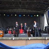 zdjęcie przedstawia burmistrza i starostów dożynek oraz konferansjera na scenie