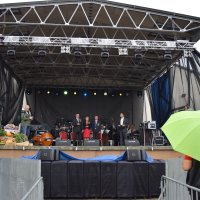 zdjęcie przedstawia scenę dożynkową na której stoją burmistrz, starostowie dożynek, konferansjer i fotograf