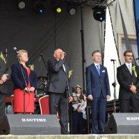 zdjęcie przedstawia grupę osób stojących na scenie, przemawia starosta dożynek