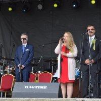 zdjęcie przedstawia trzy osoby, dwóch mężczyzn i przemawiającą do mikrofonu kobietę