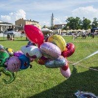 zdjęcie przedstawia kolorowe balony w różnych kształtach, w tle widać ratusz