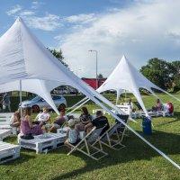 zdjęcie przedstawia namiot pod którym siedzą na leżakach ludzie