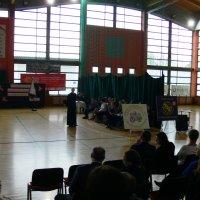 zdjęcie przedstawia halę widowiskowa-sportową w której zgromadzili się uczestnicy uroczystości, na środku stoi młody ksiądz