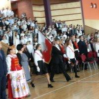 zdjęcie przedstawia halę widowiskowa-sportową w której zgromadzili się uczestnicy uroczystości; wejście pochodu sztandarowego