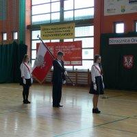 zdjęcie przedstawia halę widowiskowa-sportową w której zgromadzili się uczestnicy uroczystości; wniesienie sztandaru przez 3 uczniów z gimnazjum