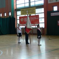 zdjęcie przedstawia halę widowiskowa-sportową w której zgromadzili się uczestnicy uroczystości; wniesienie sztandaru  ze szkoły podstawowej