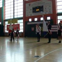 zdjęcie przedstawia halę widowiskowa-sportową w której zgromadzili się uczestnicy uroczystości: dwa poczty sztandarowe