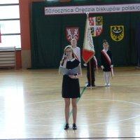 zdjęcie przedstawia halę widowiskowa-sportową którą otwiera jedna z gimnazjalistek, w tle stoi poczet sztandarowy