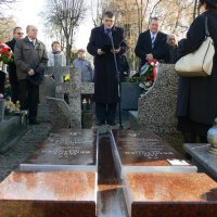 zdjęcie przedstawia przemawiającego do mikrofonu mężczyznę, na pierwszym planie pomnik