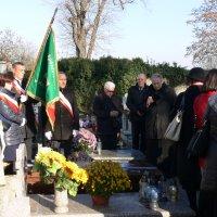 zdjęcie przedstawia grupę ludzi stojących na cmentarzu, po lewej stronie mężczyzna trzyma opuszczony sztandar
