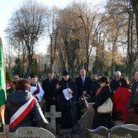 zdjęcie przedstawia grupę ludzi stojących na cmentarzu, do mikrofonu przemawiaj ksiądz